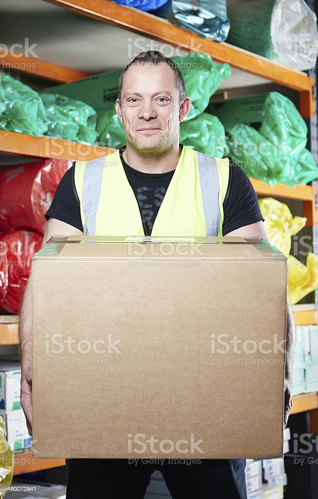 Man holding box in warehouse stock photo