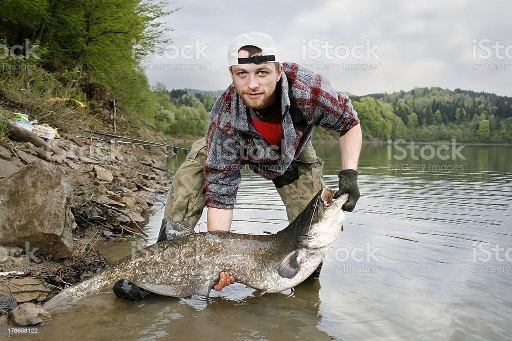 Man holding catfish he presumably caught stock photo