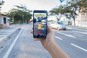 Man holding cellphone playing Pokemon Go.