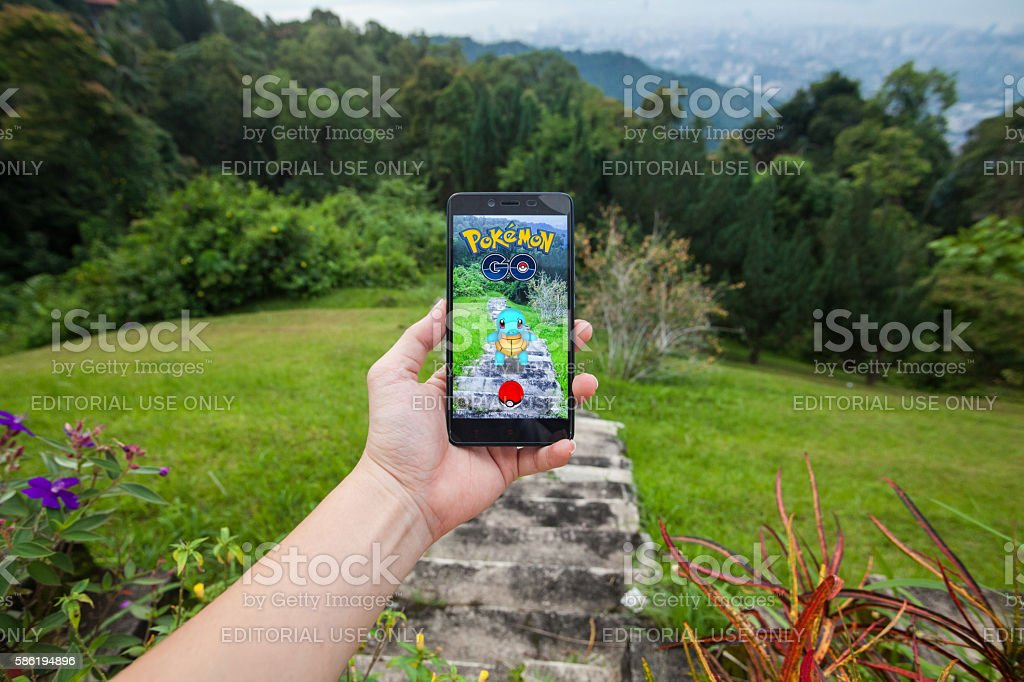 Man holding cellphone playing Pokemon Go. stock photo