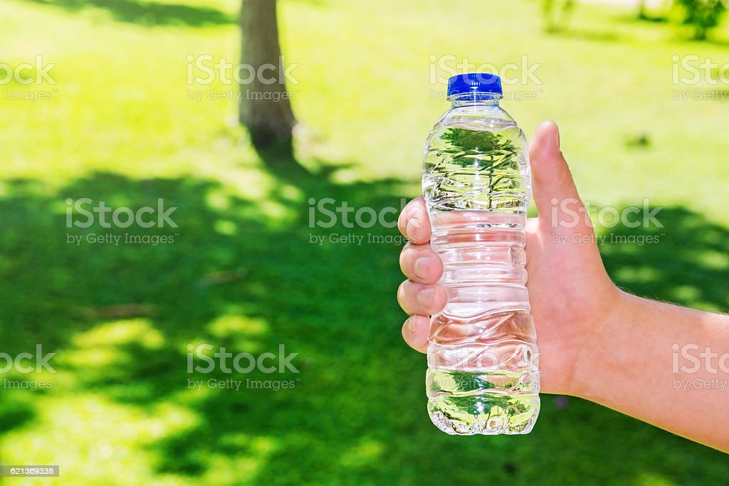 Man holding clear drinking water in a plastic bottle stock photo