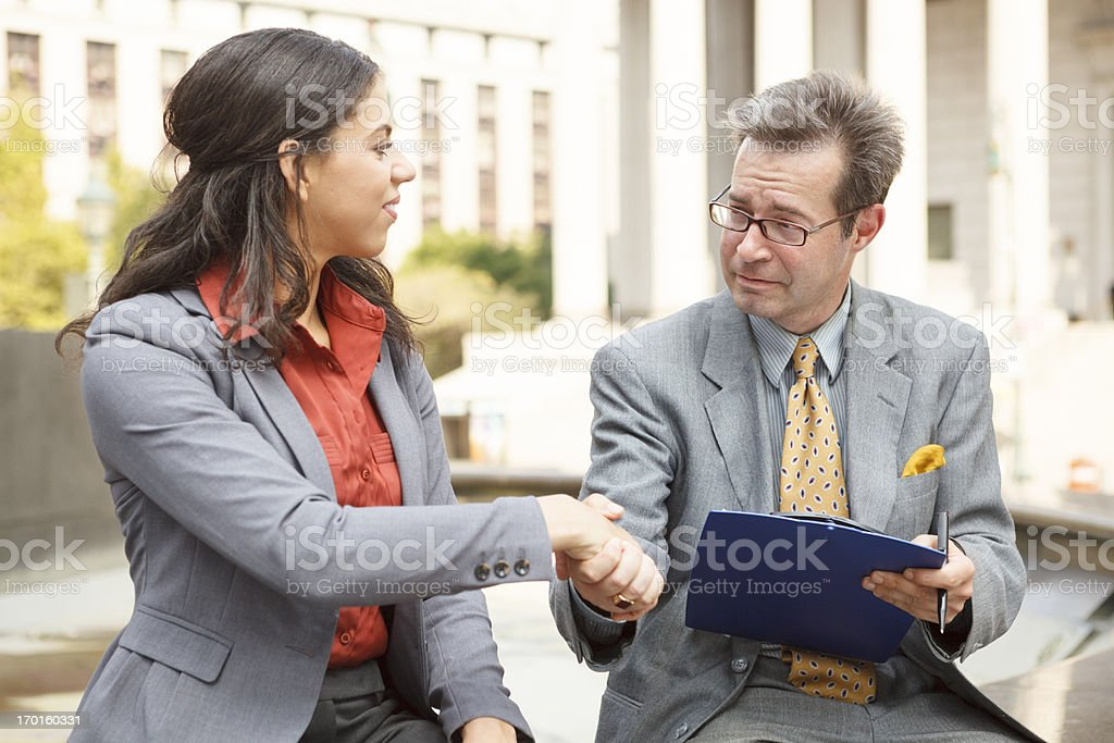 Man Holding Clipboard Shaking Hands with Woman royalty-free stock photo