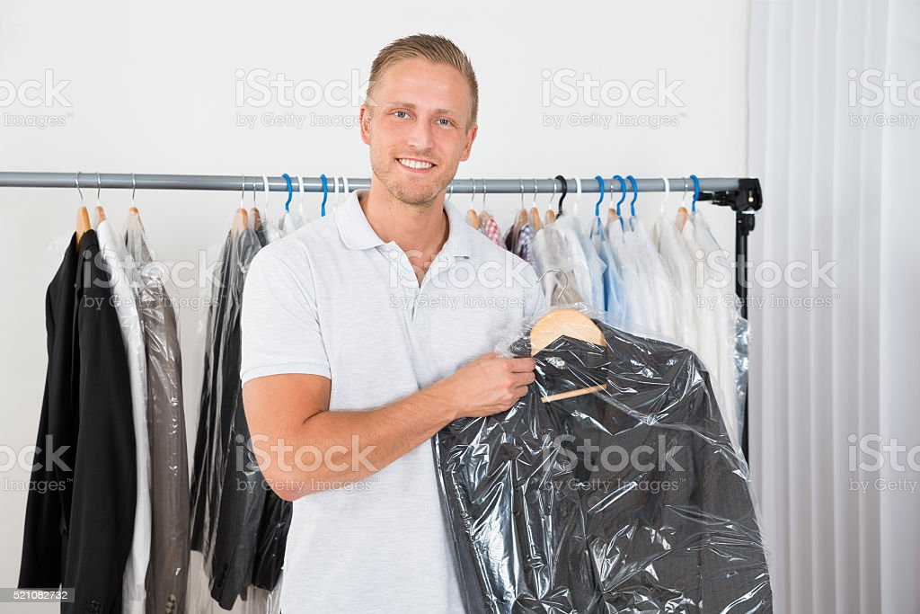 Man Holding Coat In Dry Cleaning Store stock photo
