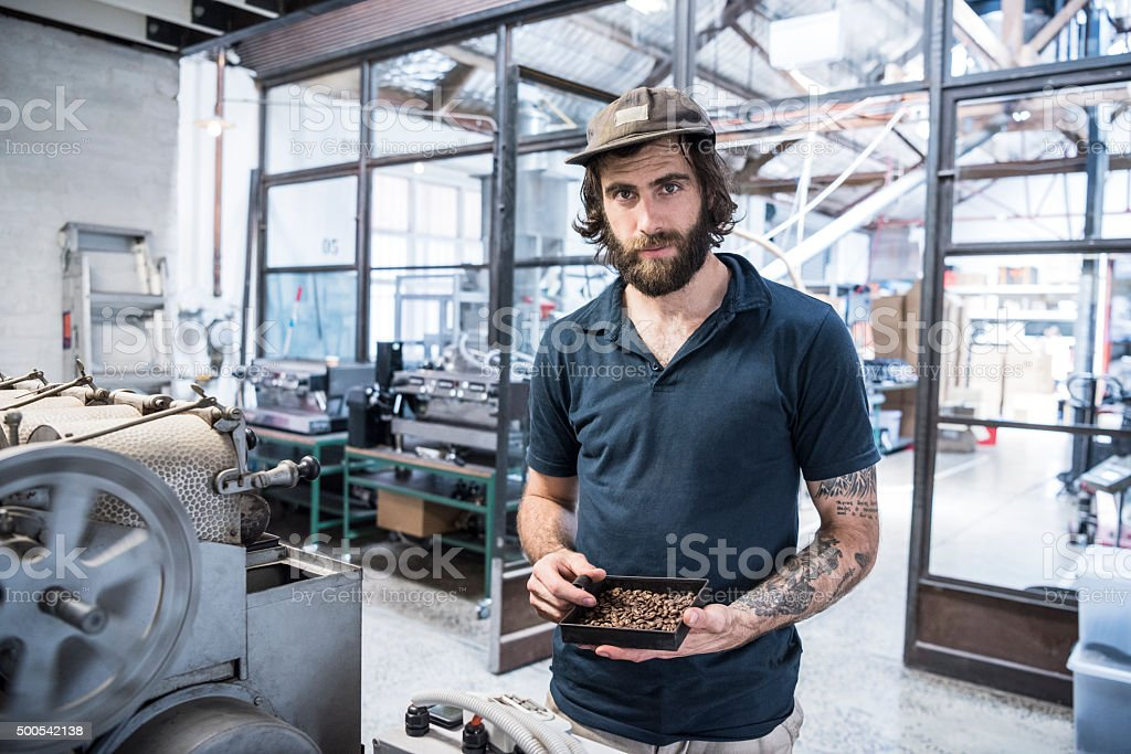 Man holding coffee beans in coffee roasting warehouse, portrait stock photo