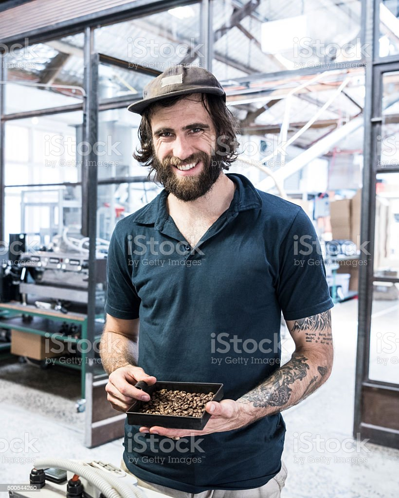 Man holding coffee beans in coffee roasting warehouse smiling, portrait stock photo