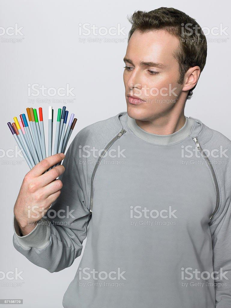 Man holding coloured pencils stock photo