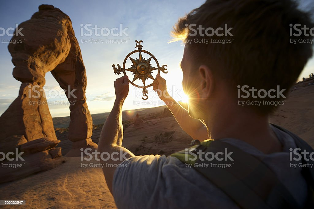 Man Holding Compass Rose at Sunset Arch stock photo
