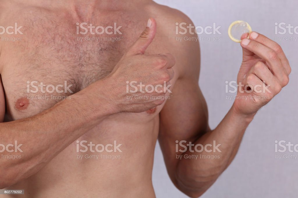 Man holding condom and showing thumbs up. Contraception, Prevention of sexually transmitted diseases. Sexual health concept. stock photo