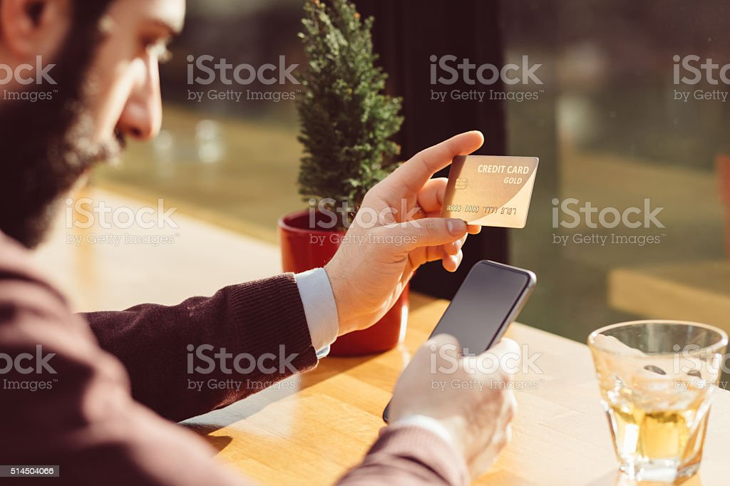 Man holding credit card and using smartphone stock photo