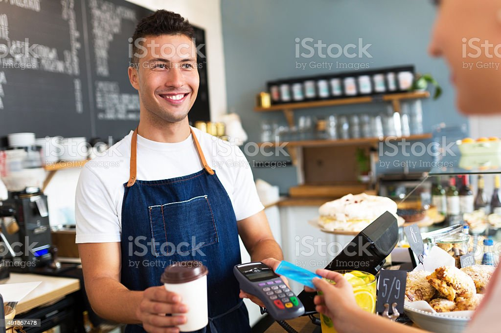 Man holding credit card reader at cafe stock photo