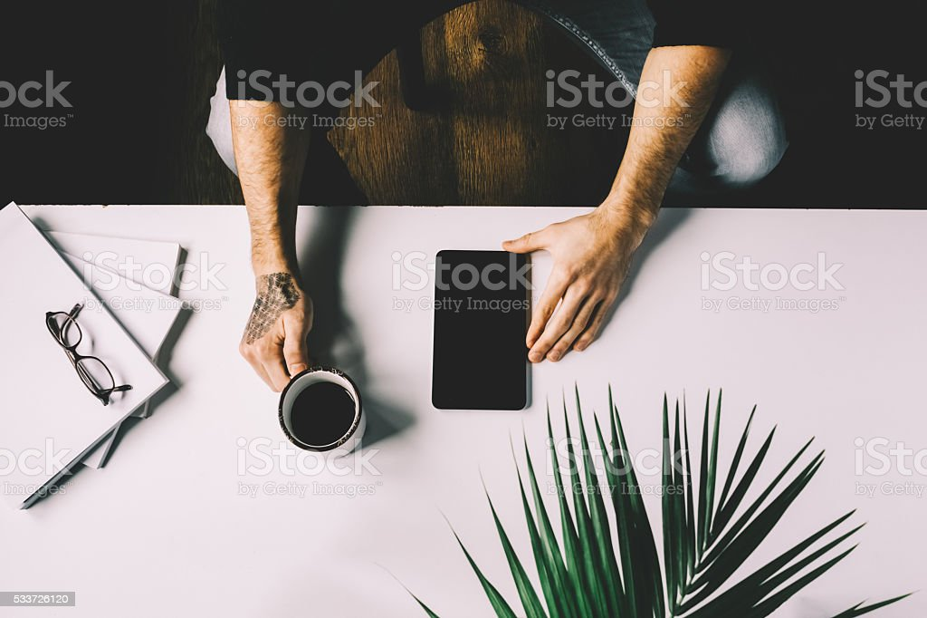Man holding cup of coffee and tablet on office desk stock photo