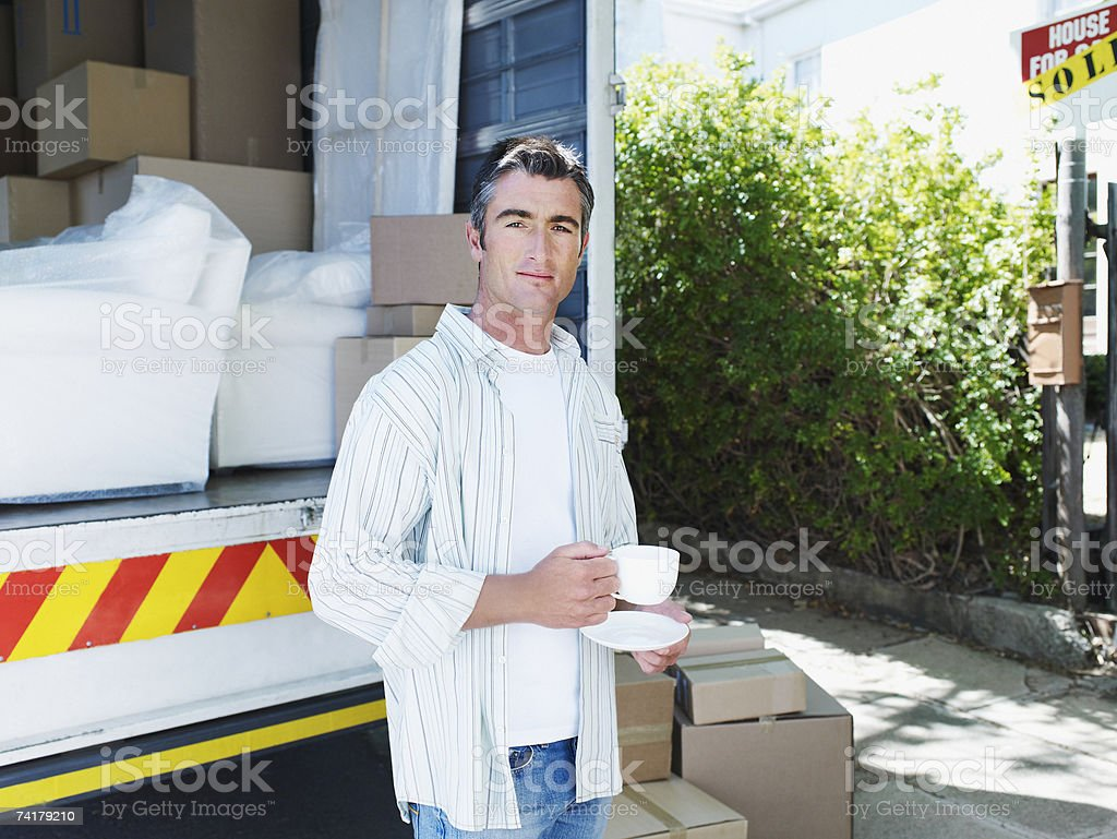 Man holding cup outdoors with moving van and boxes royalty-free stock photo
