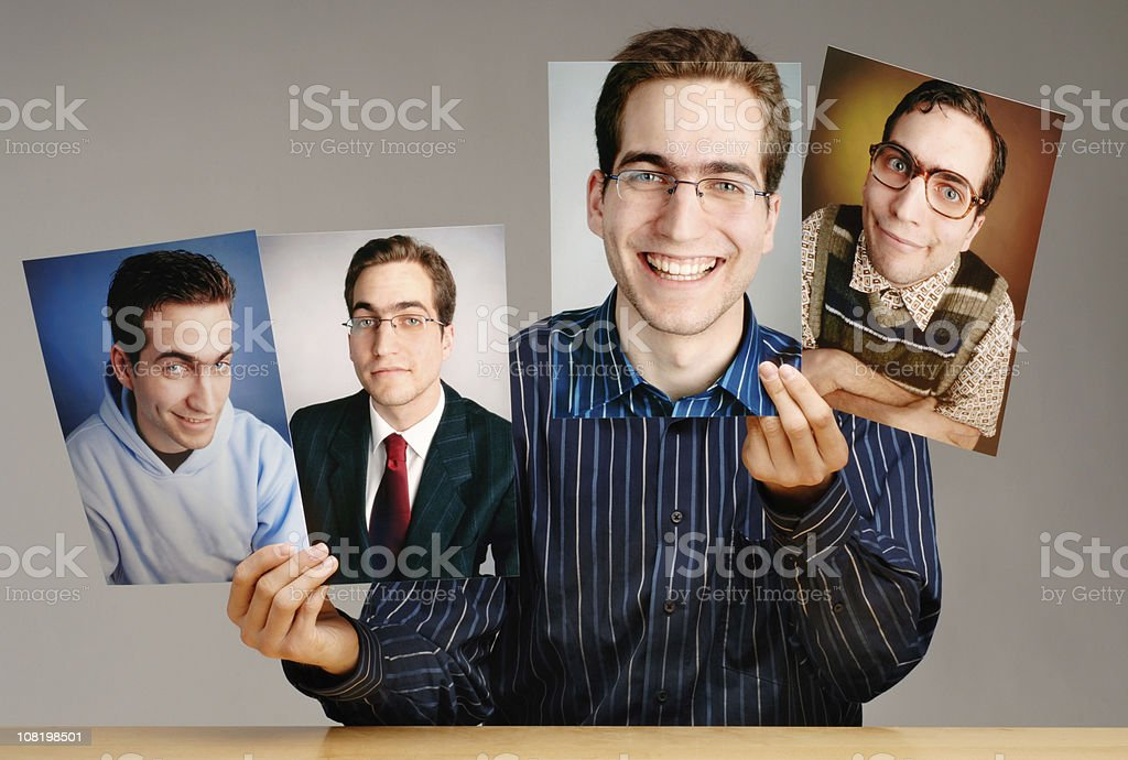 Man Holding Different Photographs of Himself stock photo