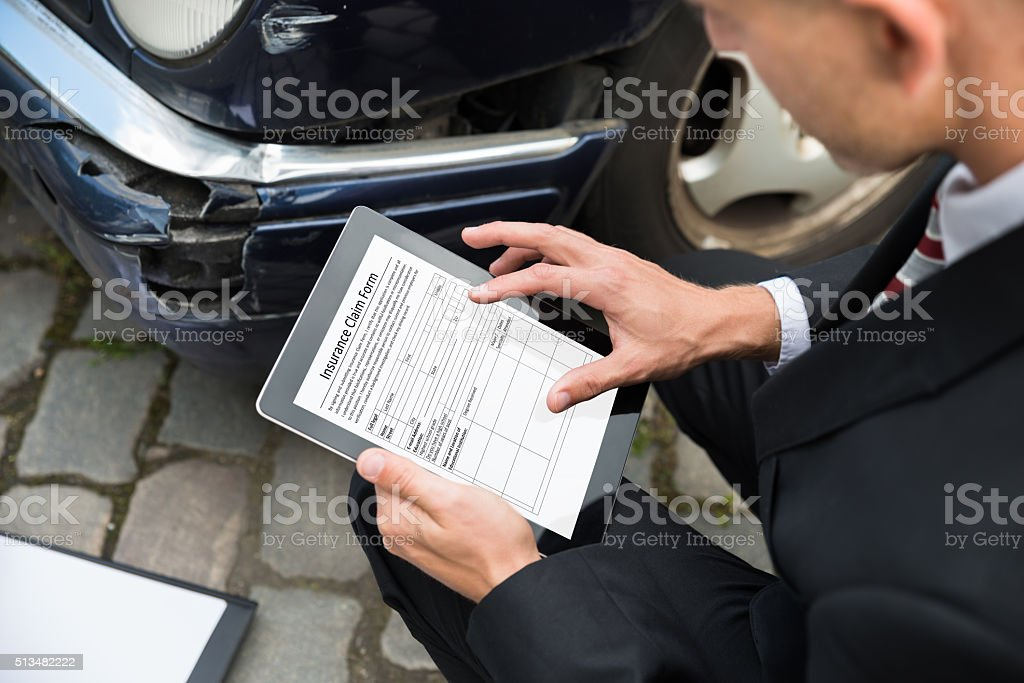 Man Holding Digital Tablet Examining Damaged Car stock photo