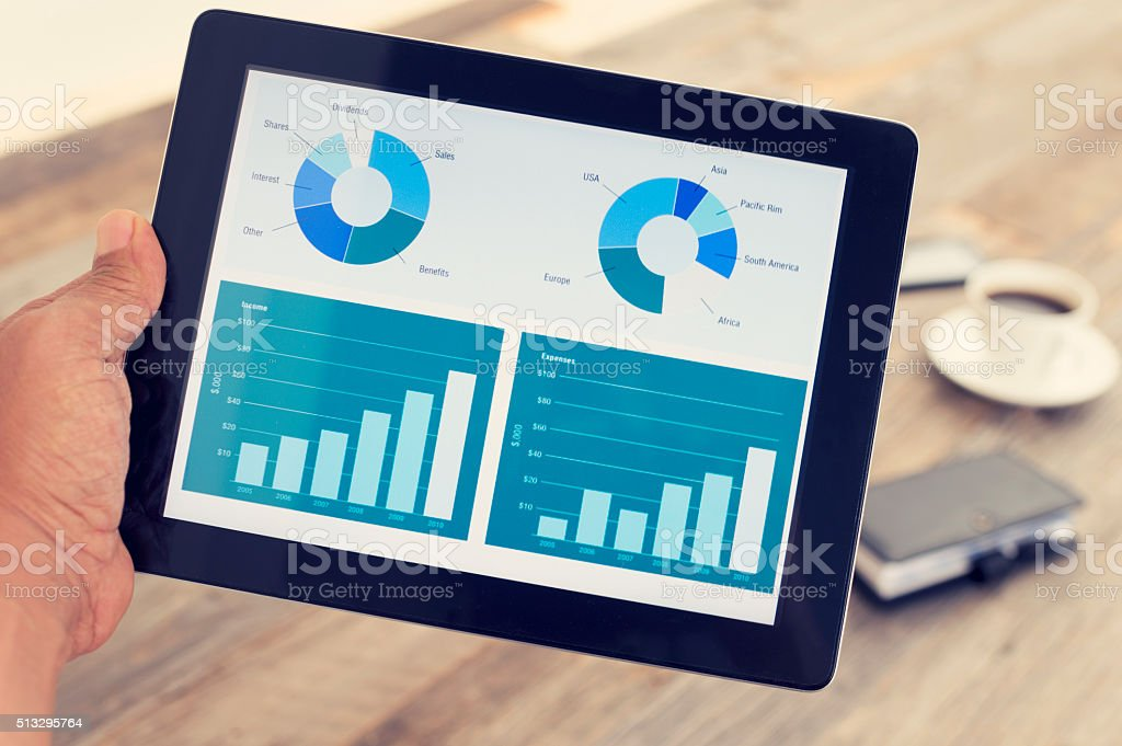 Man holding digital tablet with financial graphs and charts. stock photo
