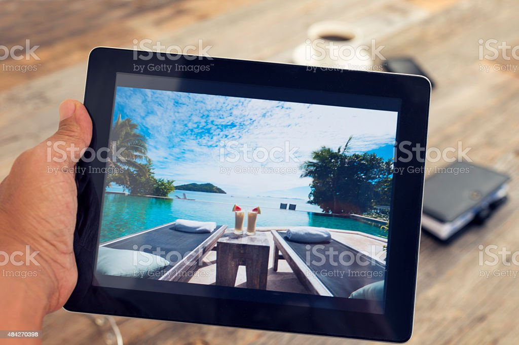 Man holding digital tablet with vacation photograph. stock photo