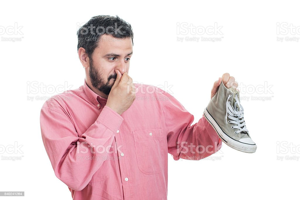 Man holding dirty stinky shoe. Unpleasant smell stink stock photo