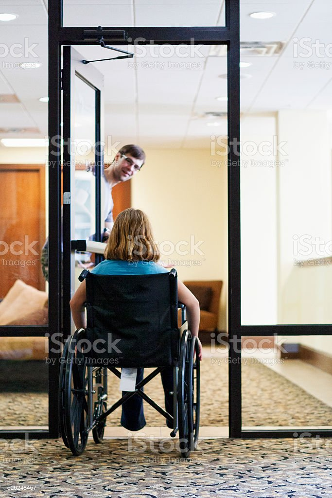 Man Holding Door for Disabled Girl in Wheelchair stock photo