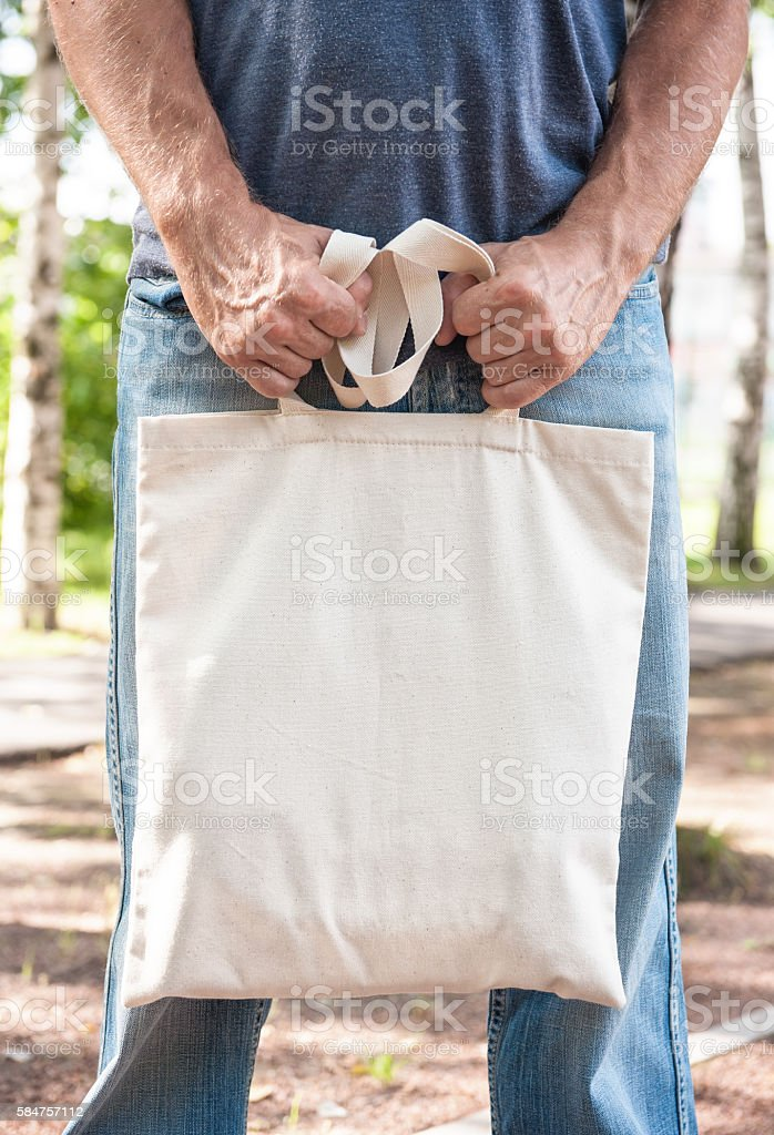 Man holding empty canvas bag. Template mock up stock photo