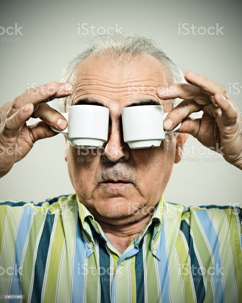 man holding espresso cups to eyes royalty-free stock photo