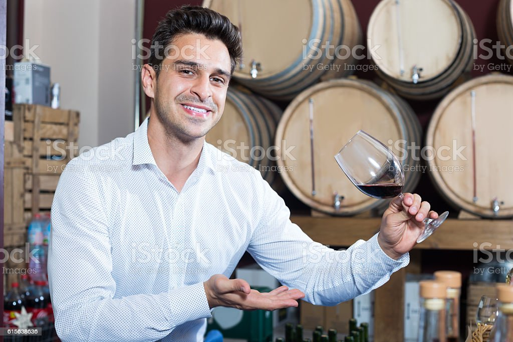 Man  holding glass of red wine in winery section stock photo