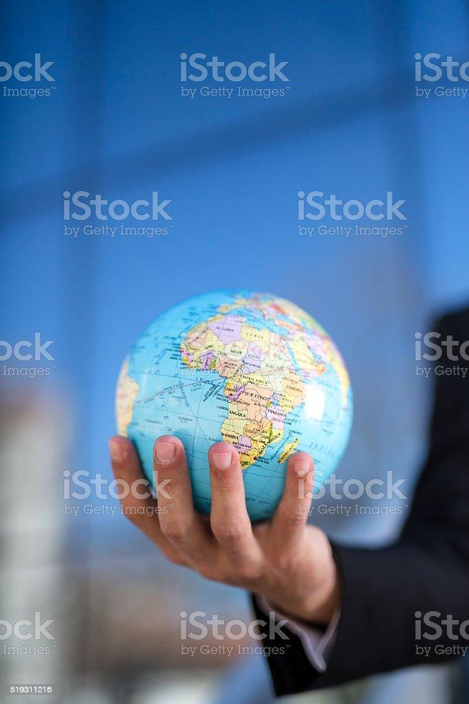 Man holding globe in hand stock photo