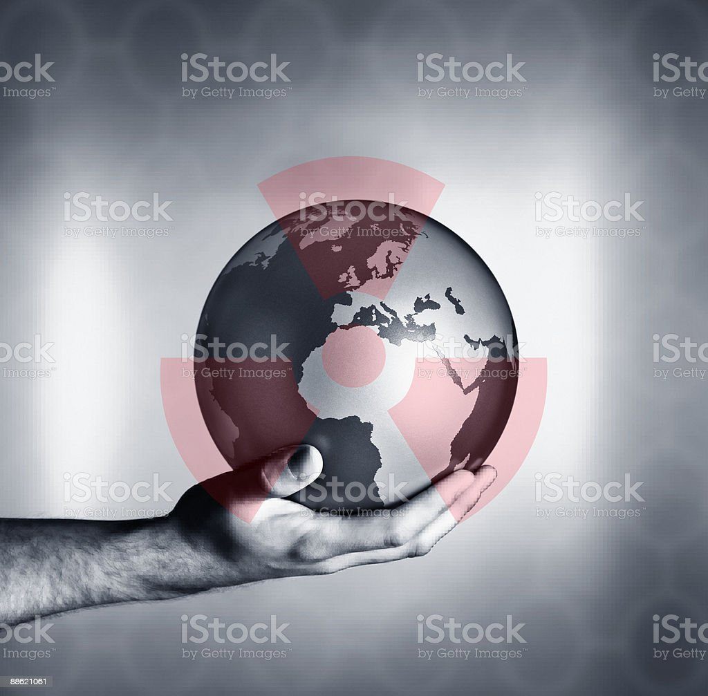 Man holding globe with overlay of nuclear symbol stock photo
