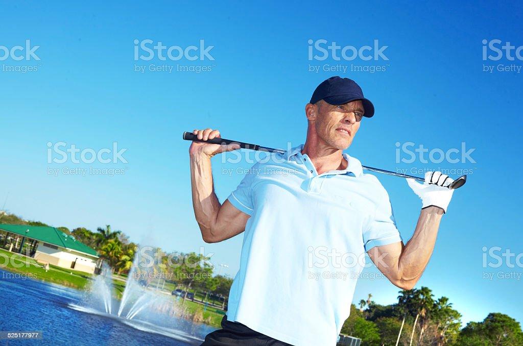 Man Holding Golf Club Against Clear Blue Sky stock photo