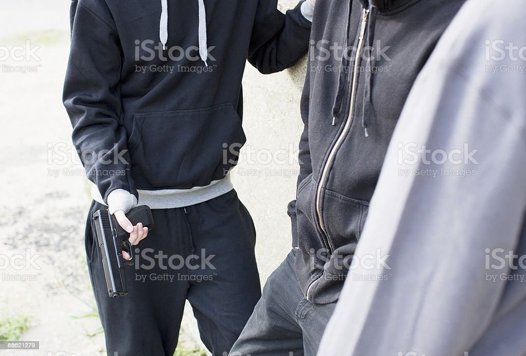 Man holding gun and standing with friends royalty-free stock photo