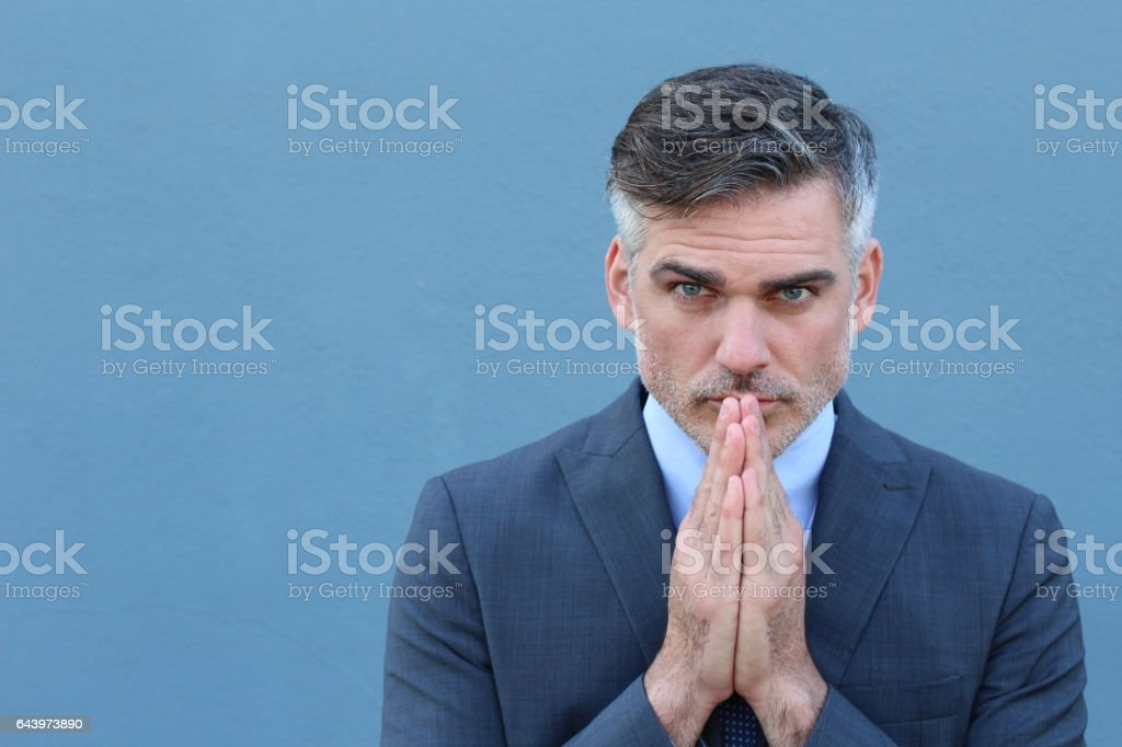 Man holding hands clasped near face stock photo