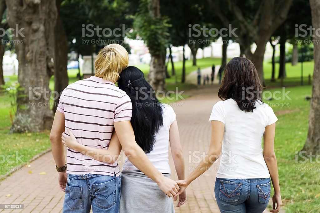 Man holding hands with a woman while another woman holds him stock photo