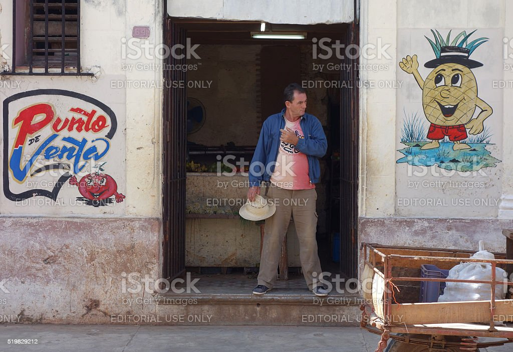man holding hat standing in doorway of store stock photo