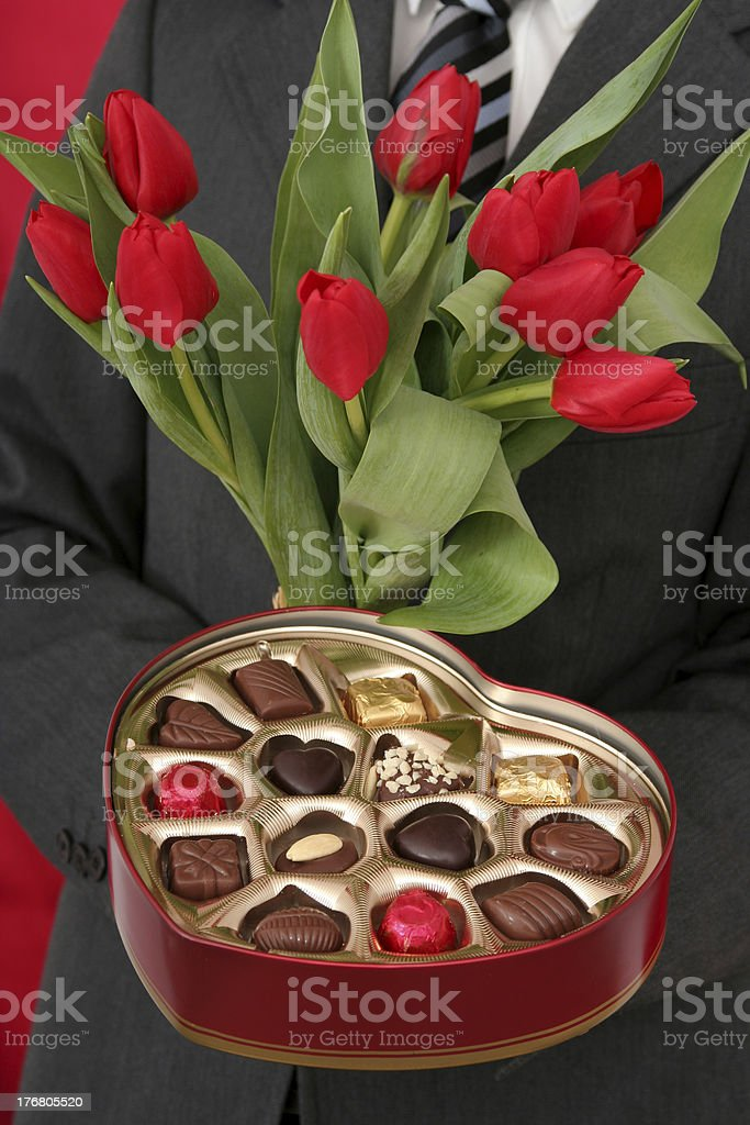 Man Holding Heart Shaped Box of Candy and Red Tulips royalty-free stock photo