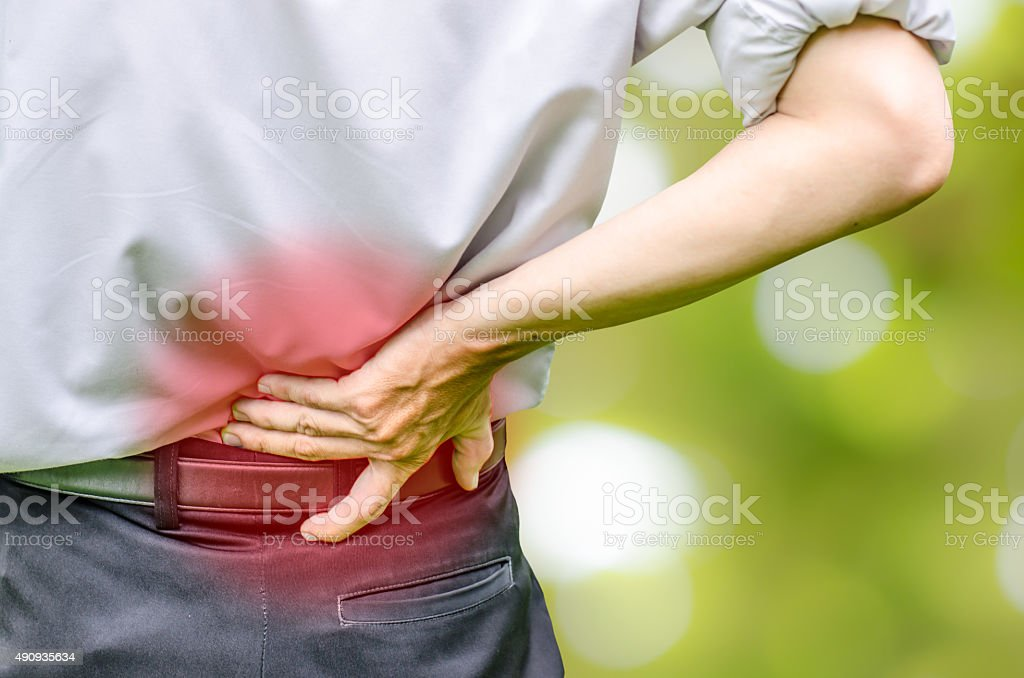 Man holding his back in pain. stock photo