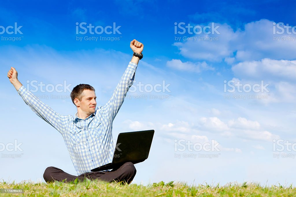 A man holding his hands up celebrating with laptop on lap royalty-free stock photo