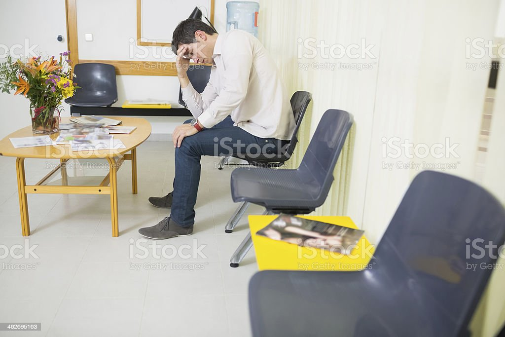 Man holding his head while sitting on a chair stock photo