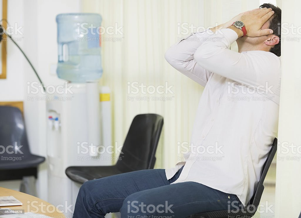 Man holding his head with two hands stock photo