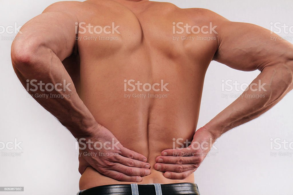 Man holding his lower back. Pain relief concept stock photo