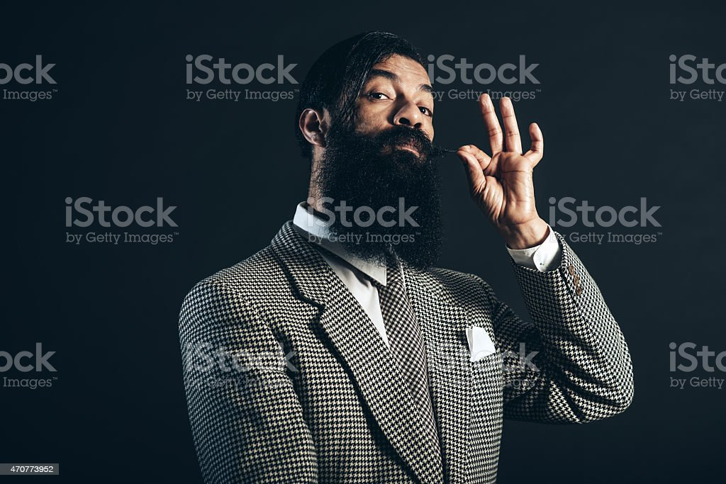 Man Holding his Mustache While Looking at Camera stock photo