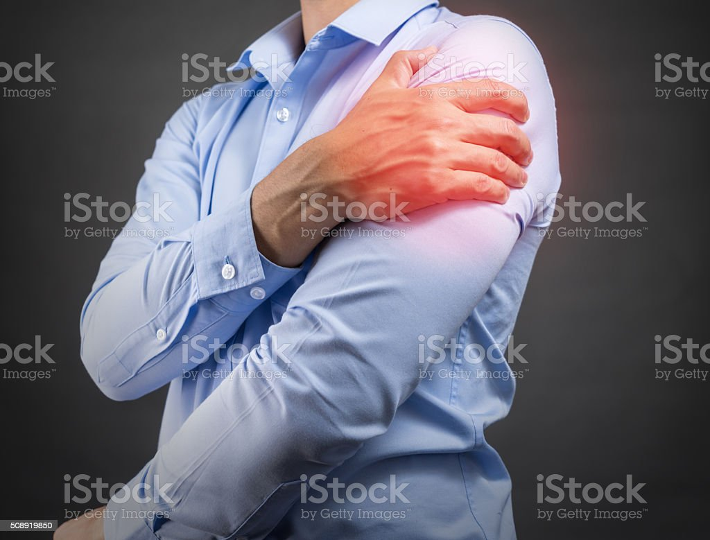 man holding his shoulder in pain stock photo