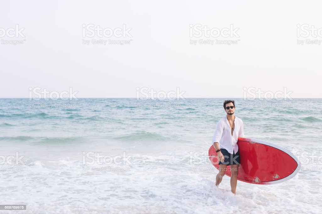 Man holding his surfboard stock photo