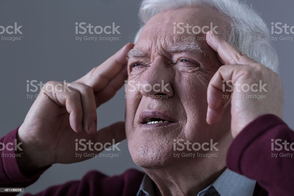 Man holding his temples stock photo