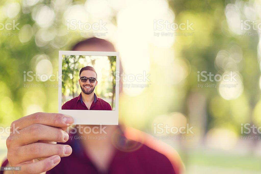 Man holding instant selfie stock photo