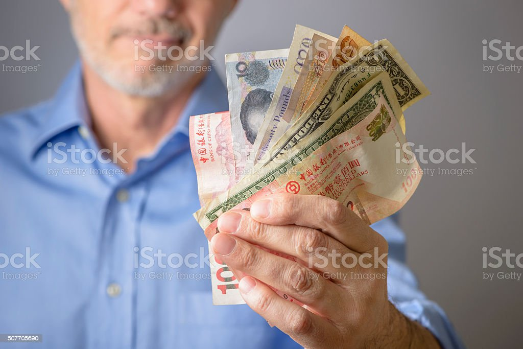 Man Holding International Currency Bank Notes stock photo