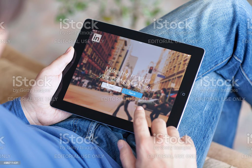 Man holding iPad with App LinkedIn on the screen stock photo