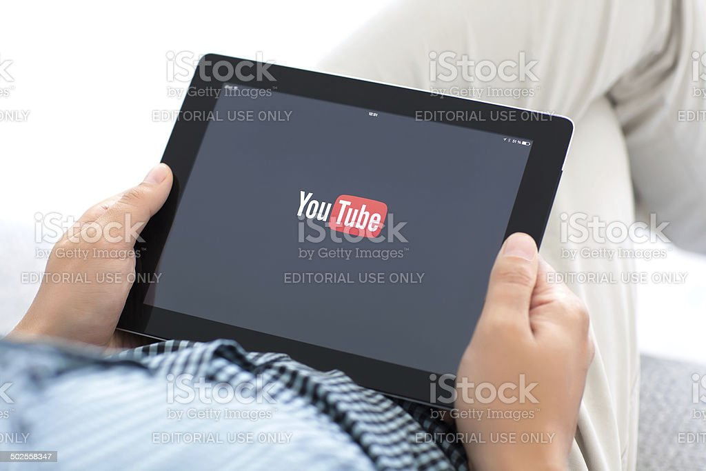 man holding iPad with app YouTube on the screen stock photo