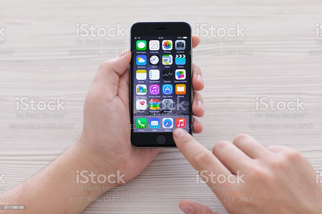 man holding iPhone 6 Space Gray over the table stock photo
