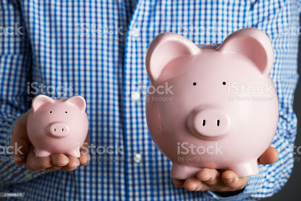 Man Holding Large And Small Piggy Bank stock photo