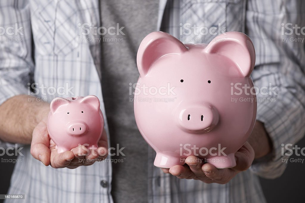Man Holding Large And Small Piggy Banks stock photo