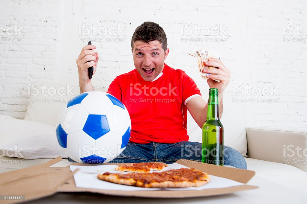 man holding mobile phone and money watching television internet gambling stock photo